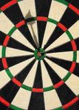 Dart at Bullseye. Professional dartboard and a dart shooting bullseye stock image