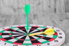Dart on center of dartboard Stock Photo