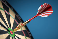 Dart in center of the target dartboard. Closeup. Stock Photos