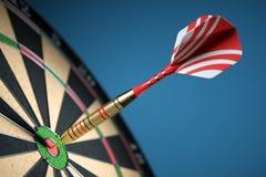 Dart in center of the target dartboard. Closeup. Stock Photos