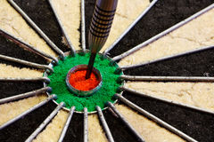 Dart in the centre bulls eye. A dart hits target in the centre of a darts board good business concept for success Stock Image