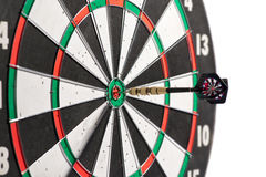 Dart in the centre of a dart board. Scoring a bulls eye conceptual of winning, accuracy, skill, challenge and achievement, isolated on white Royalty Free Stock Image