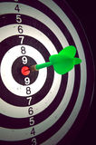 Dart in darts target against a dark background Royalty Free Stock Photography