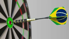Dart featuring flag of Brazil hits bullseye of the target. Sports or political success related conceptual 3D rendering. Dart featuring flag hitting bullseye of Stock Image