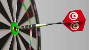 Dart featuring flag of Tunisia hits bullseye of the target. Sports or political success related conceptual animation. Dart featuring flag hitting bullseye of the stock footage
