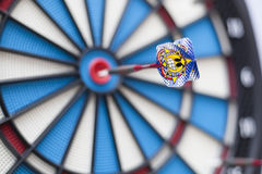 Dart with a grinning emoticon hit bullseye with the emoticon in focus and background blurry Royalty Free Stock Photos