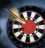Dart heading for Dartboard with a large bulls eye. Stock Photo