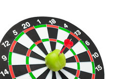 Dart hit green apple in the target centre Royalty Free Stock Photos