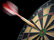 Dart hit a target dartboard in motion. Closeup Stock Photos