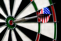 Dart hitting bullseye on dartboard Stock Photo