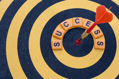 Dart hitting the bullseye target with word success on dartboard Royalty Free Stock Photo