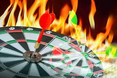 Dart hitting on center with fire on dartboard for business concept. Red Dart on bitcoin with fire flames smoke, Right on target concept using dart in the bulls stock photography