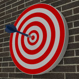 Dart hitting center target on dartboard Royalty Free Stock Images