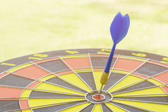 Dart hitting in target center of dartboard Stock Photo