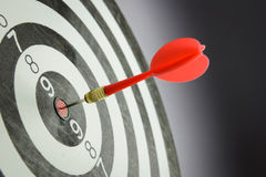 Dart. Meet target concept using dart pinned at the bullseye of dartboard Stock Images