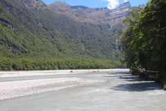 Dart River with people in the distance who do rafting along the river, New Zealand royalty free stock photo