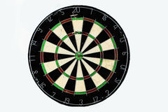 Dart strikes the bulls-eye of a dartboard. A dart strikes the bulls-eye of a dartboard. Wide shot of a dart board from below, three darts with a bulls eye Royalty Free Stock Photo