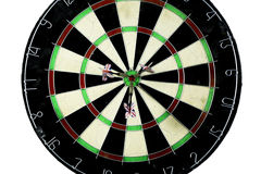 Dart strikes the bulls-eye of a dartboard Stock Photography