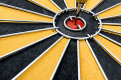 Dart target with arrow on the center of dartboard Royalty Free Stock Photos