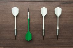 Dart uniqueness concept. Green dart uniqueness concept on brown wooden background Stock Photos