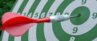 Dartboard με ένα κόκκινο βέλος στο κέντρο Στοκ εικόνες με δικαίωμα ελεύθερης χρήσης