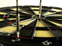 DartBoard. With two darts stuck in it. One of the darts is in the bullseye. Dart in foreground is out of focus. Focus is on bullseye dart Royalty Free Stock Photography