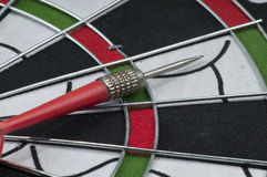 Dartboard and arrow. Closeup on isolated area Royalty Free Stock Image