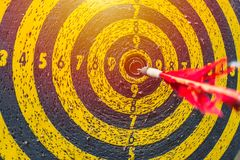 Dartboard with arrow at center after many times attempt. Hard to win but don`t stop to try concept: old dartboard with arrow at center after many times attempt Royalty Free Stock Photo