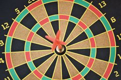 Dartboard and arrow. Closeup of a cork dartboard and arrow in the bullseye Stock Images