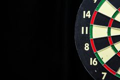 Dartboard on Black. Partial red, green, black, and cream dartboard on black with copyspace on left Royalty Free Stock Images