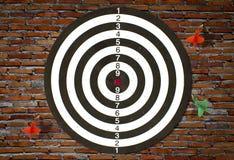 Dartboard on brick wall Stock Image