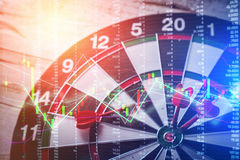 Dartboard business strategy ideas concept. Right on target concept using dart in the bullseye on dartboard with business graph analysis success concept Stock Photos