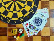 Dartboard with cards and dice on chessboard Royalty Free Stock Photos