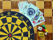 Dartboard with cards and dice on chessboard Stock Images