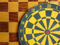 Dartboard with cards and dice on chessboard Royalty Free Stock Images
