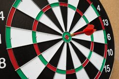 Dartboard. Dart arrow hitting in the target center of dartboard Stock Photography