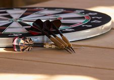 Dartboard and darts. Dartboard and six darts on wooden table Royalty Free Stock Photo