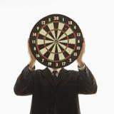Dartboard de fixation d'homme devant le visage. photographie stock libre de droits