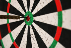 Dartboard detail. Close-up of a dartboard with a dart in the bull's eye Royalty Free Stock Photos