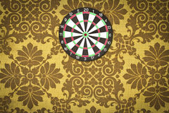Dartboard on fabric wallpaper. Royalty Free Stock Image