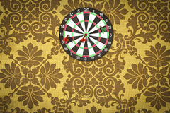 Dartboard on fabric wallpaper. Stock Images