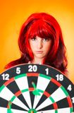 Dartboard Girl 4. Teenage girl with red wig holding a dartboard in front of her Stock Images
