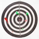 Dartboard hanging up with several darts Stock Photography