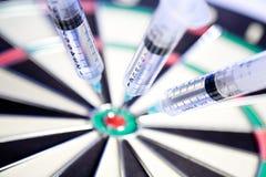 dartboard klibbade injektionssprutor Arkivfoton