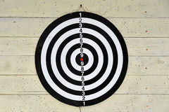 Dartboard on a light yellow background. With traces of Darts Royalty Free Stock Photos