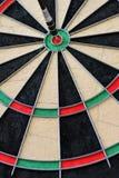 Dartboard met pijltje in het centrum stock afbeelding