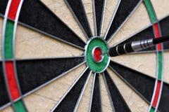Dartboard met pijltje in het centrum stock foto's