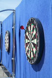 Dartboard with one javelin on blue wall on street Royalty Free Stock Photography