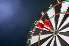 Dartboard op een blauwe achtergrond met pijlen die het centrum Ta raken Stock Afbeelding