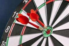 Dartboard op een blauwe achtergrond met pijlen die het centrum Ta raken Stock Fotografie